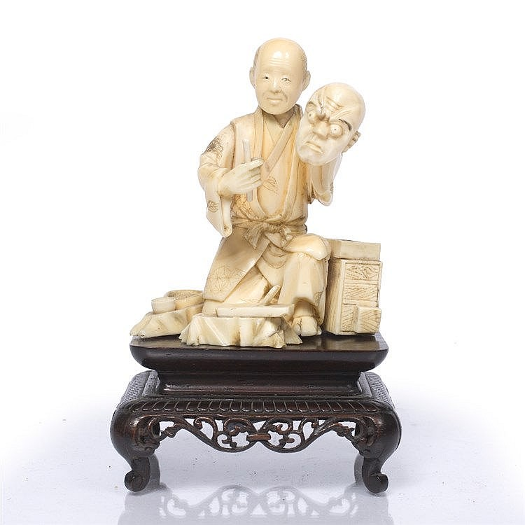 A Japanese ivory okimono of semi-kneeling antisam holding a noh mask and a tool