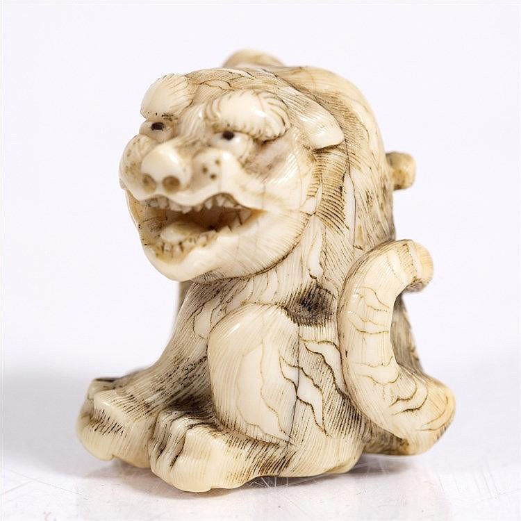 A Japanese ivory netsuke of a seated tiger