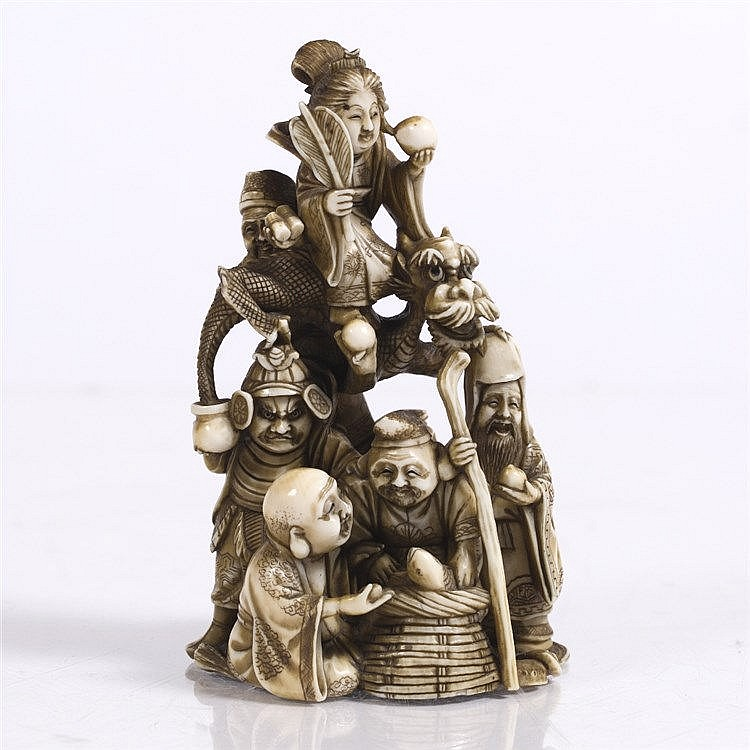 A Japanese ivory okimono carved as a pyramid depicting the Shichifukin
