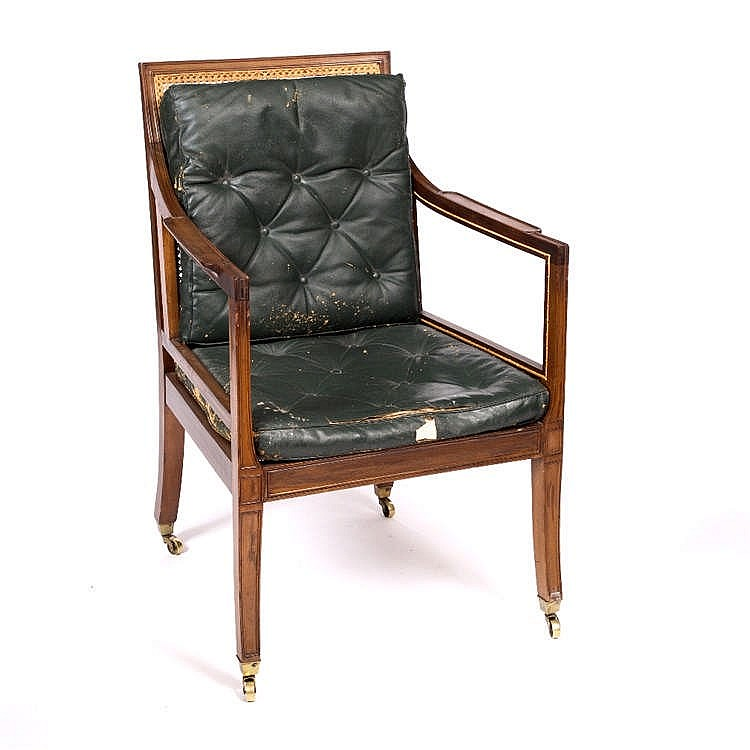 A REGENCY STYLE MAHOGANY BERGERE LIBRARY ARMCHAIR with green leather cushio