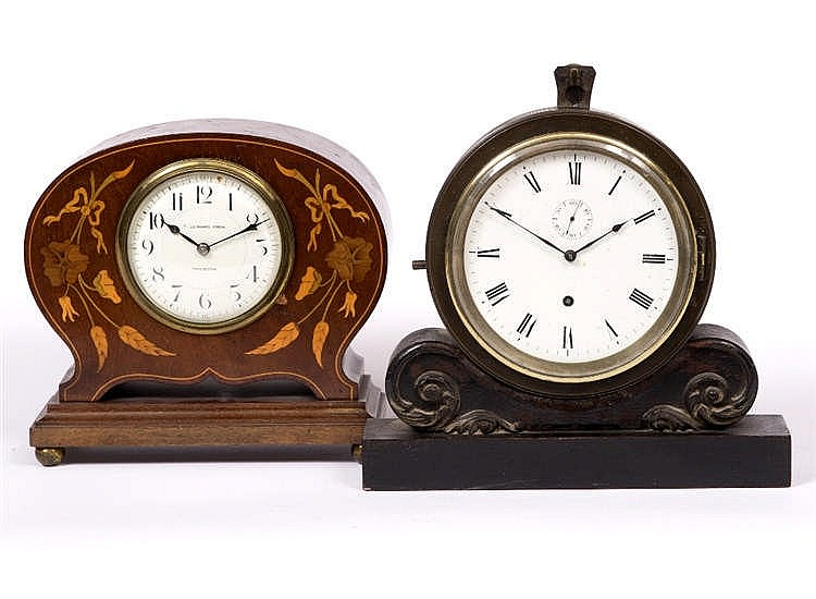 A BRONZE CASED MANTEL CLOCK with white enamel dial, suspended on an ebonise
