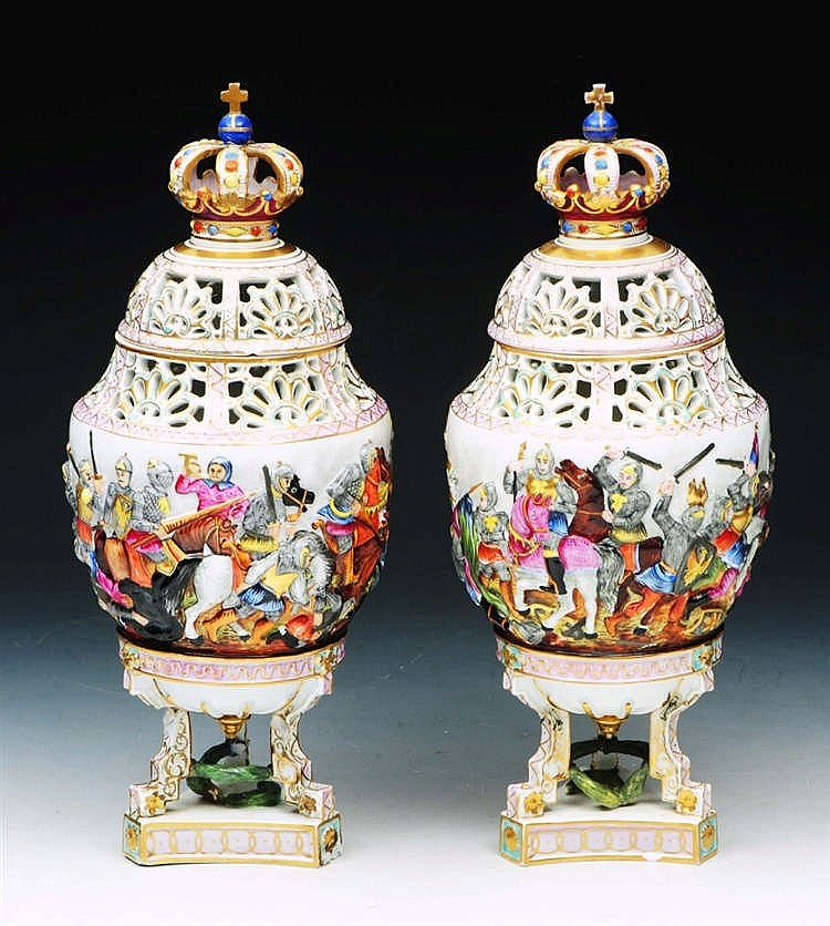 A PAIR OF CAPO DI MONTE URNS AND COVERS each moulded and painted with a con