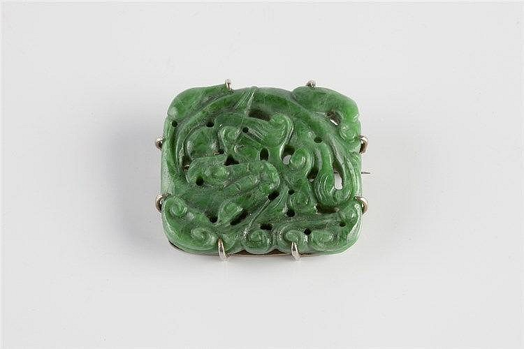 A Chinese spinach jade brooch 19th Century with foliate scroll design