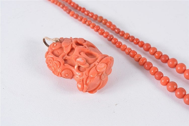 A Chinese carved coral pendant 19th/20th Century with foliate carving