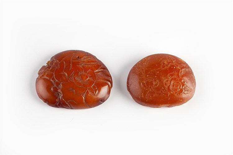 Two Chinese amber roundels/mounts 17th/18th Century carved with flower