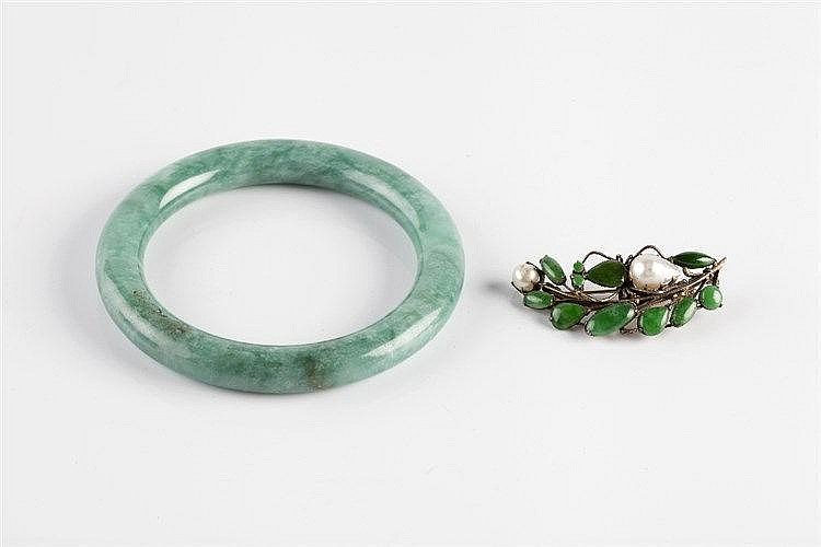 A Chinese green hardstone bangle 19th/20th Century and a jade and pear