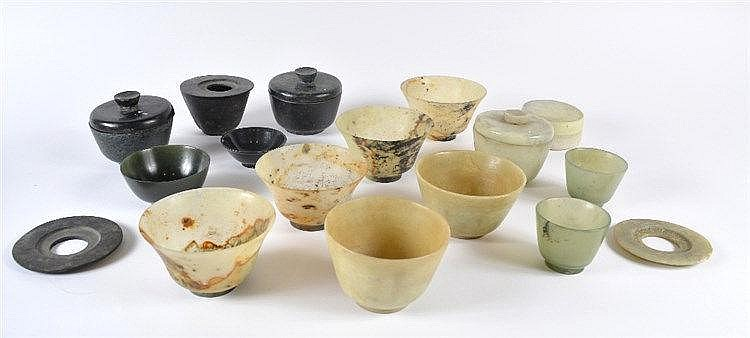 A collection of eleven Chinese bowenite bowls and four black stone and
