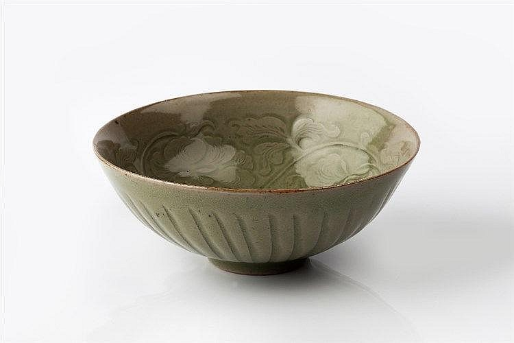 A Chinese celadon bowl carved peony flowers, foliage and tendrils arou