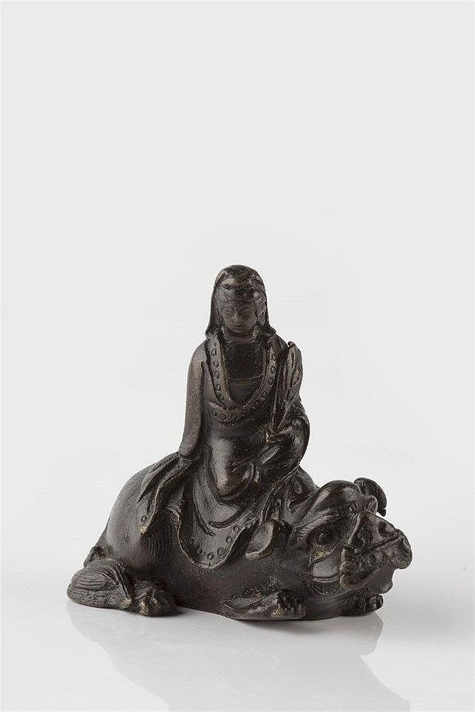A Chinese bronze scroll weight modelled as Guanyin riding a mythical c