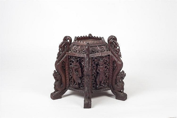 A Burmese hexagonal carved stand 19th Century with various deities to