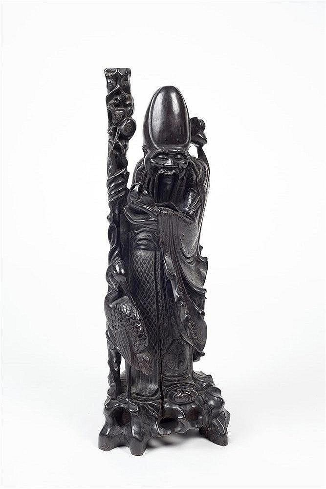 A Chinese hardwood caved figure of Shou Lao standing aside a crane hol