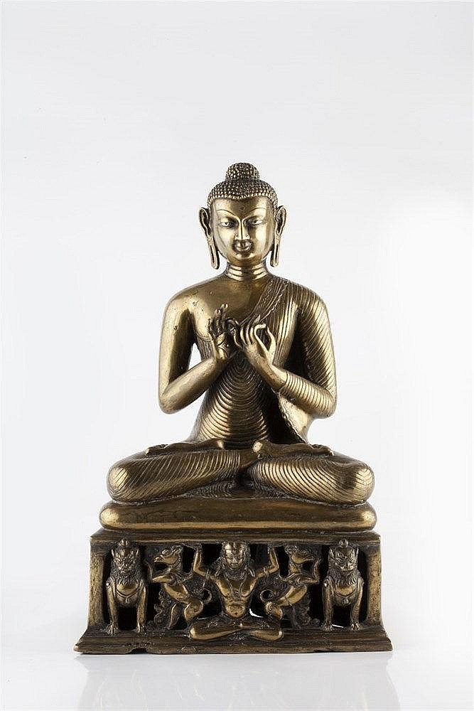 A Chinese bronze seated Buddha 18th/19th Century the base having a cen