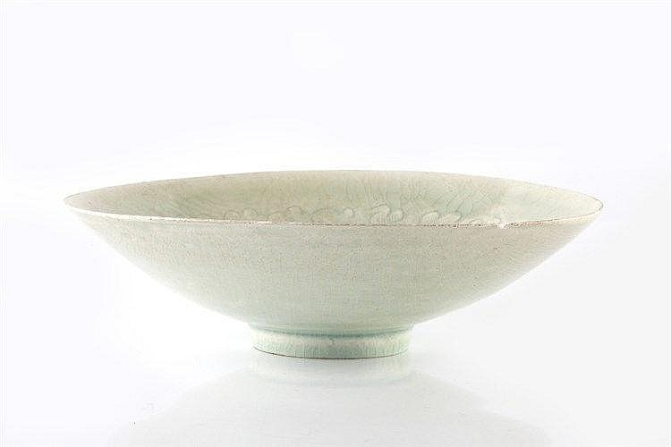 A Chinese pale celadon dish 17th Century with wave designs of tapering