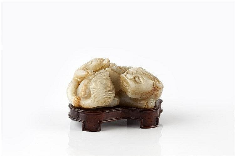 A Chinese white jade pebble late Ming carved as a reclining kylin