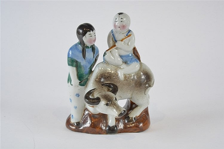 A Chinese porcelain figural group of a youth with flute seated upon a