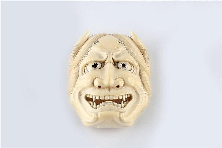 A carved ivory netsuke mask of Hannya early Meiji signed Ryumin,