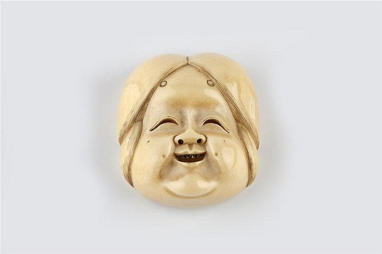 An ivory netsuke mask of a smiling Okame mid Meiji period signed