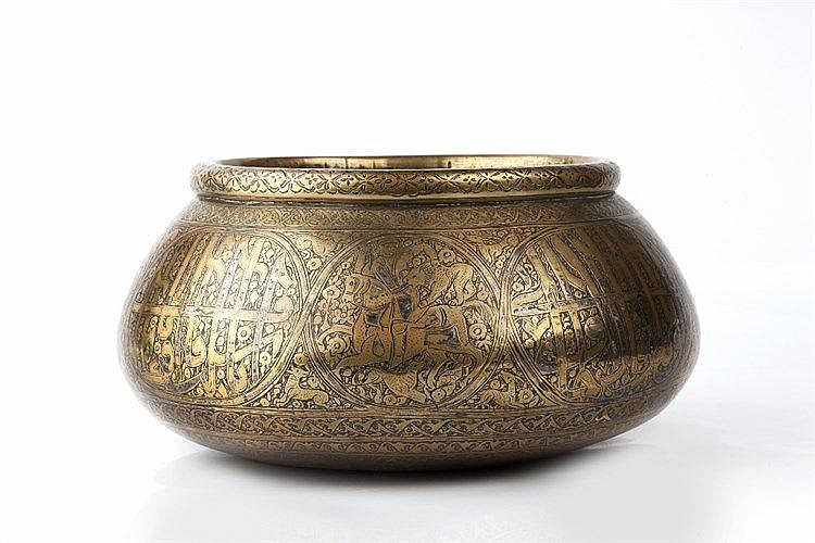 A Qajar silver inlaid brass bowl engraved with borders of figures, ani