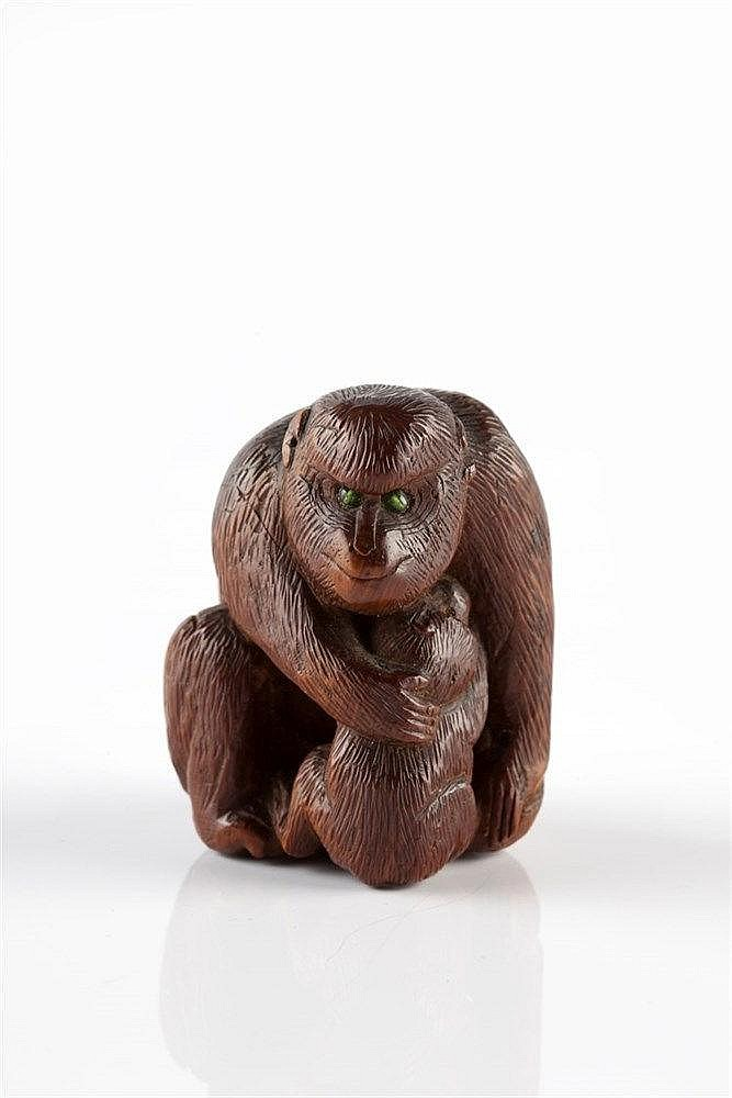 A Japanese wood netsuke late Meiji of a squatting monkey nursing