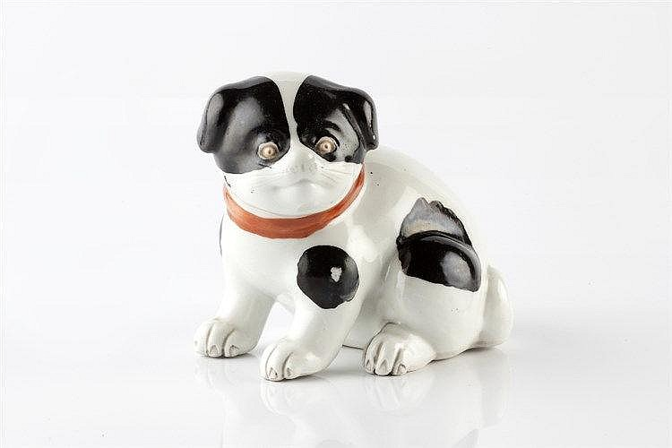A Japanese porcelain model of a puppy circa 1900 with red ribbon