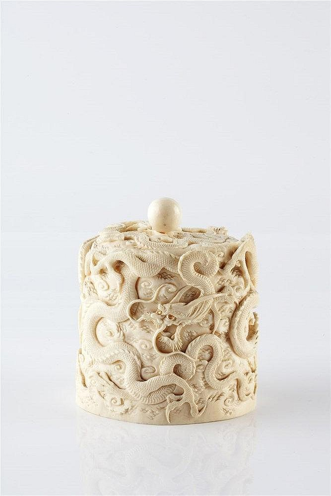 A Japanese ivory box and cover Meiji period carved in high relief