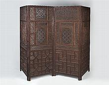 An Indian hardwood fourfold screen with intricate fret work panels dec
