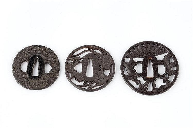 Three Japanese Tsubas the first tsuba depicting flower and foliage, si
