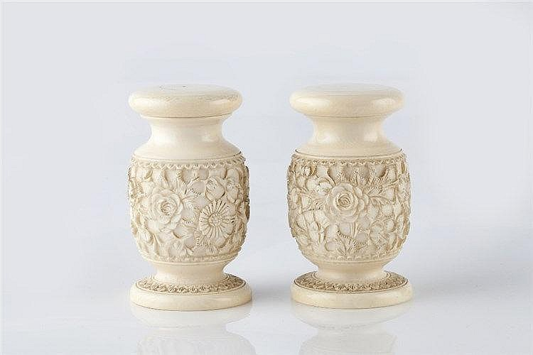 A pair of Indian carved ivory containers circa 1900 with relief b
