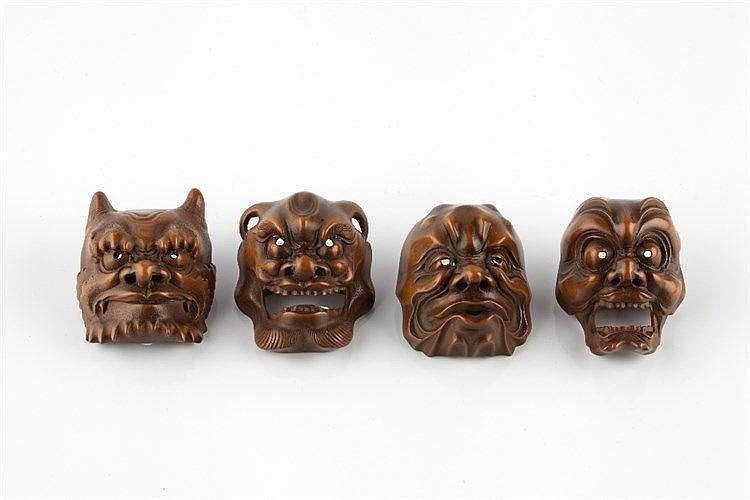 A group of four boxwood netsuke masks Meiji period Oni with accentuated e
