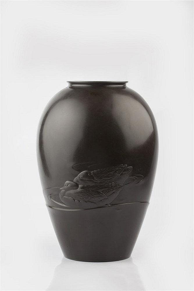 A Japanese bronze vase Meiji period carved in high relief with tw