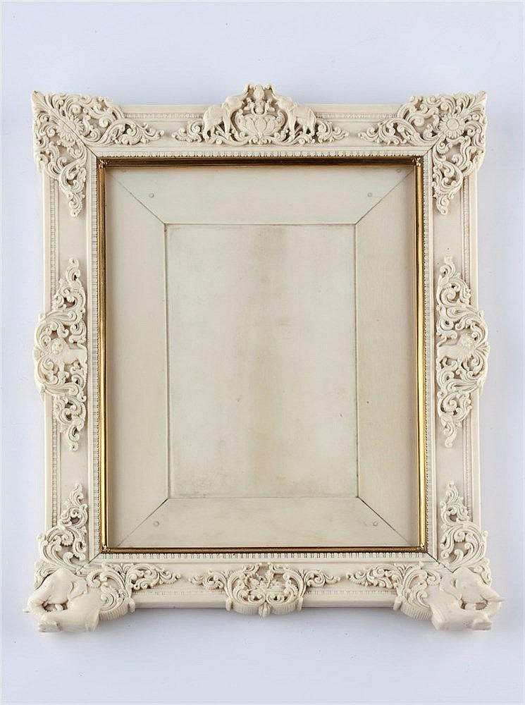 An Indian ivory carved frame 19th Century the border having a central