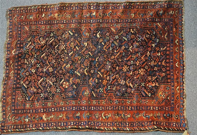 A Khamseh Rug of red ground form, the centre displaying animals and me