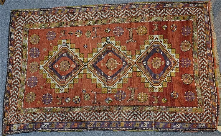 A Kazak rug of red ground, with three central medallions with a center