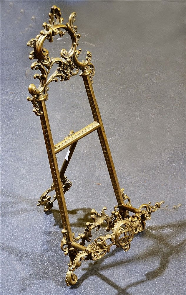 A GILT BRASS TABLE EASEL of Rococo scroll and pierced form, 54cm high and a