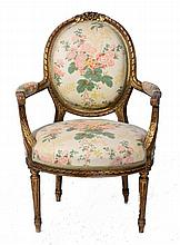 A FRENCH GILTWOOD FAUTEUIL with floral printed cover and ribbon swag orname