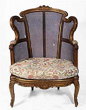 A LARGE FRENCH GILTWOOD ARMCHAIR with scrolling foliate ornament, cane seat