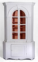AN ANTIQUE WHITE PAINTED FREE STANDING CORNER CABINET with panelled base, 1
