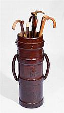 A GROUP OF WALKING STICKS, riding crops etc., within a leather cartridge ca