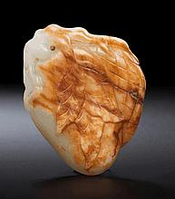 A WHITE AND RUSSET JADE LYCHEE PENDANT