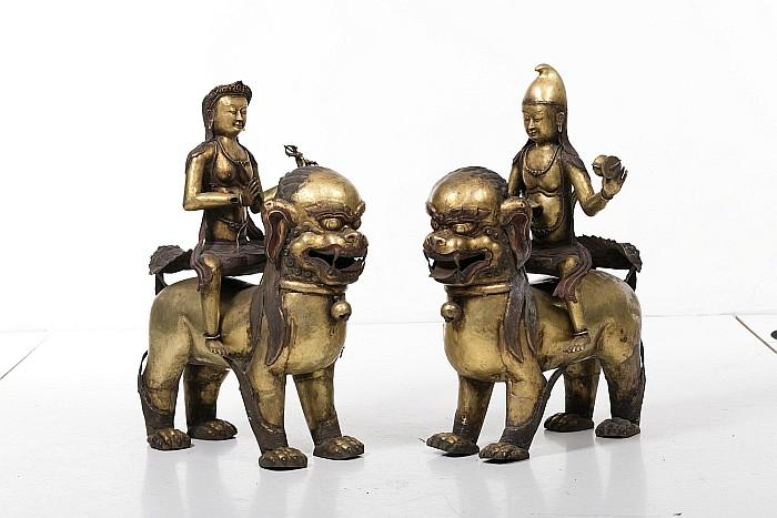 Tibetan gilt copper Lama and Bodhisattva figures riding qilin