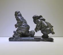 Two figures running next to seal - sculpture
