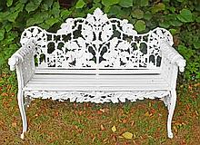 A FINE HEAVY CAST IRON GARDEN BENCH,  the arched back, with scrolling oak b