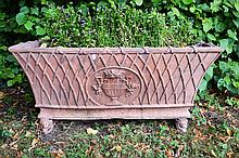 A RECTANGULAR TERRACOTTA GARDEN PLANTER,  with a reeded edge, above a taper