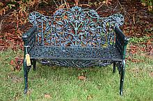 A PAIR OF HEAVY CAST IRON AND GREEN PAINTED RUSTIC GARDEN BENCHES,  each wi