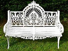 A PAIR OF HEAVY CAST IRON PIERCED ARCH BACK GARDEN BENCHES,  each with a pi