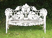 A HEAVY CAST IRON GARDEN BENCH,  the arched back cast and pierced with scro