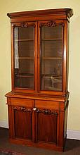 A VICTORIAN MAHOGANY BOOKCASE,  the moulded cornice, above two glazed doors