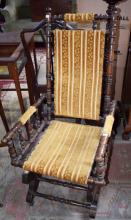 AN EDWARDIAN ROCKING CHAIR,  covered in old brocad