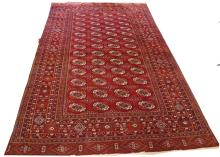 A RED GROUND BOKHARA RUG , with four rows of octag