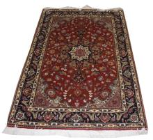 A FINE PART-SILK PERSIAN RUG, the iron red field w